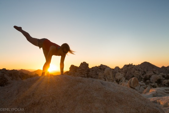 Woman doing yoga on big granite rock at Joshua Tree National Park at sunset.