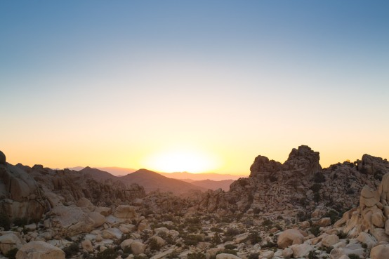 Sun setting over rock formations at Joshua Tree National Park.
