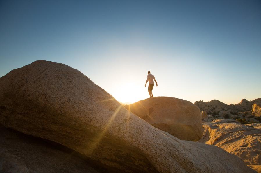 Man doing yoga on round rock at Joshua Tree at sunset.