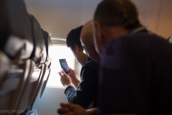 Tourists taking pictures out airplane window to Leh.