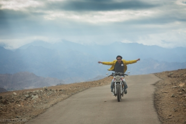 Ladakhi man riding motorcycle with no hands on the roads around Leh.