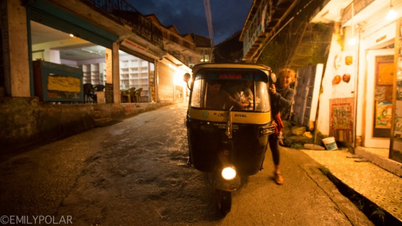 Woman getting into tuk tuk in the streets of Vashisht at dusk.