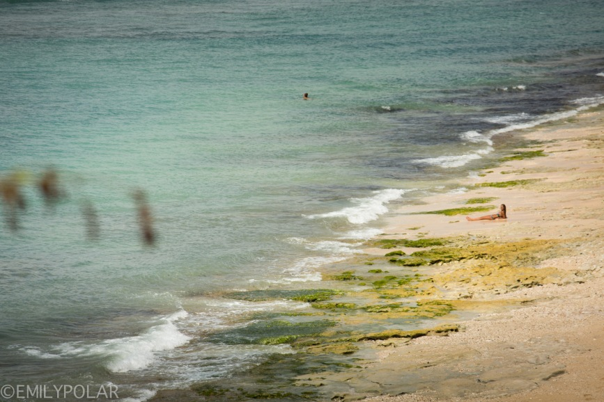 Woman laying alone on the beach in Bingin, South Kuta, Bali.