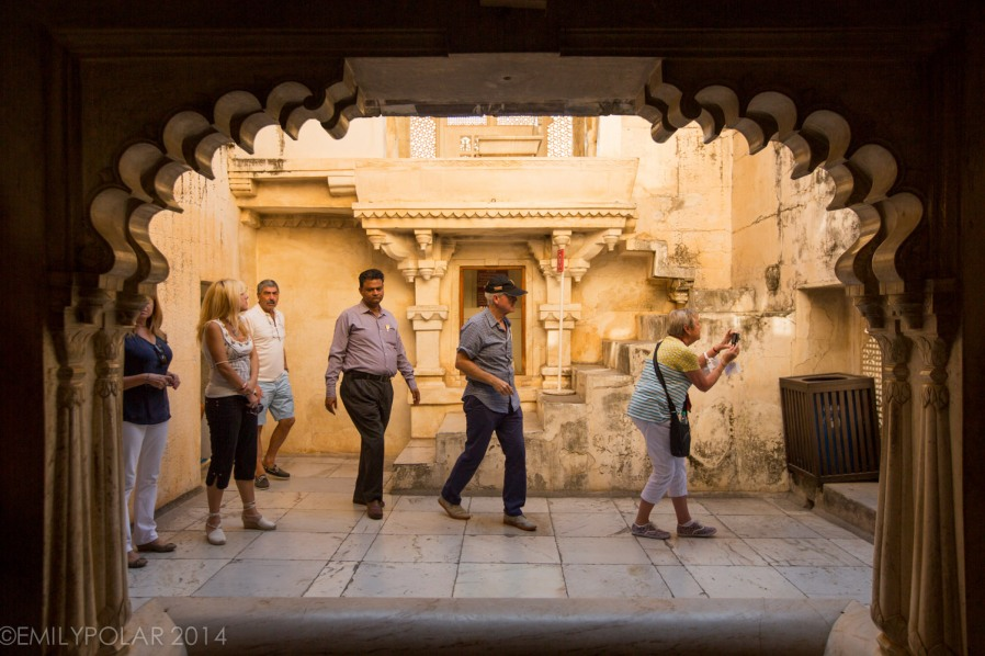 Indian guide walking with Western tourists through the City Palace in Udaipur.