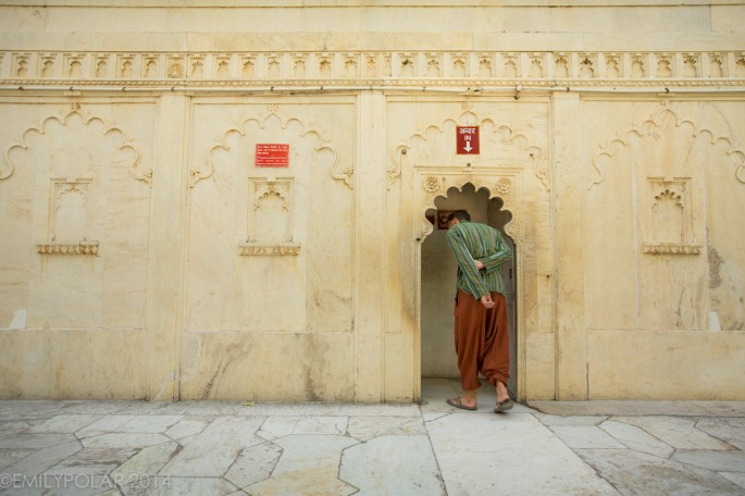 Tall western man walking through arch doorway into the City Palace in Udaipur.