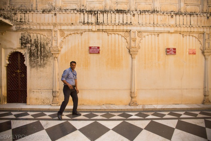 Indian man walking akwardly along one of the City Palace walls in Udaipur.