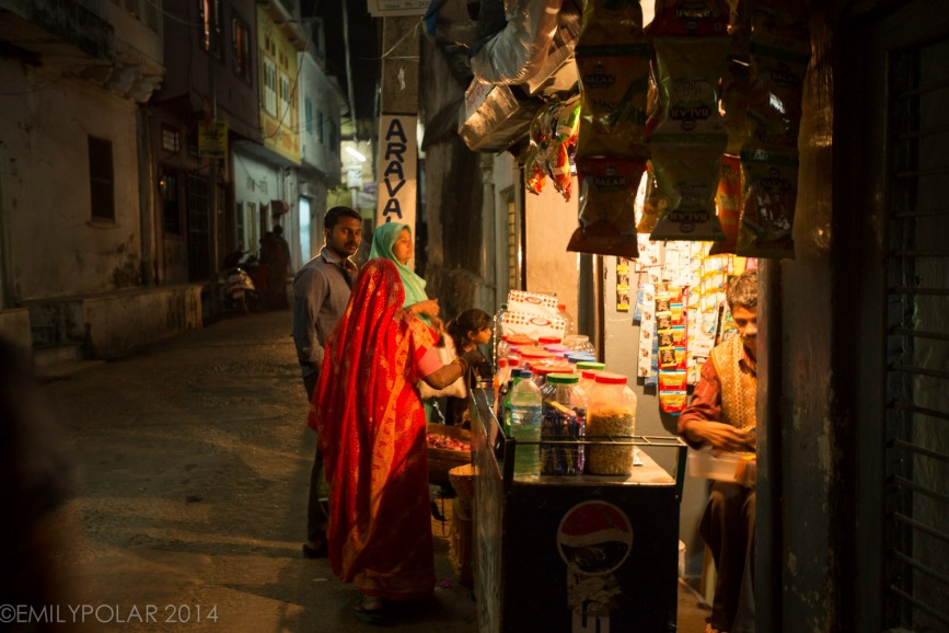 Women buying from local street shop in the night streets of Udaipur.