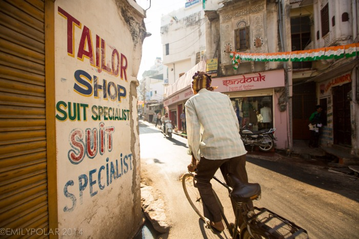 Indian man riding bicycle into the morning sun in Udaipur.