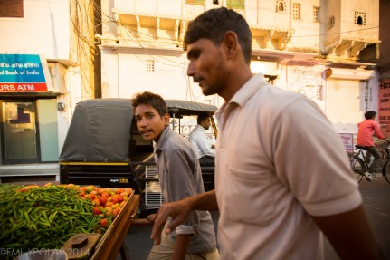 Indian men pushing street cart with vegetables at sunset in Udaipur.