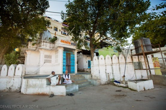 Two Indian men sitting outside of small temple in Udaipur.