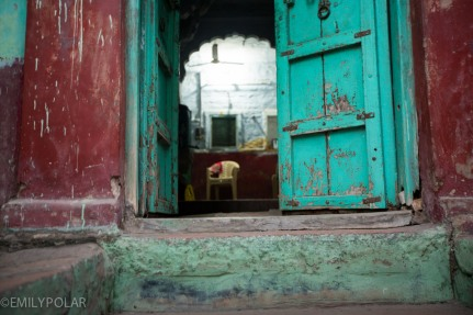 Stairs leading through the colorful doors of a home in Jodhpur, India.