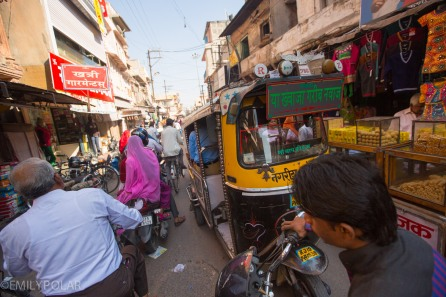 Busy street with people, rickshaws moving past the shops in Jodhpur, Rajasthan.