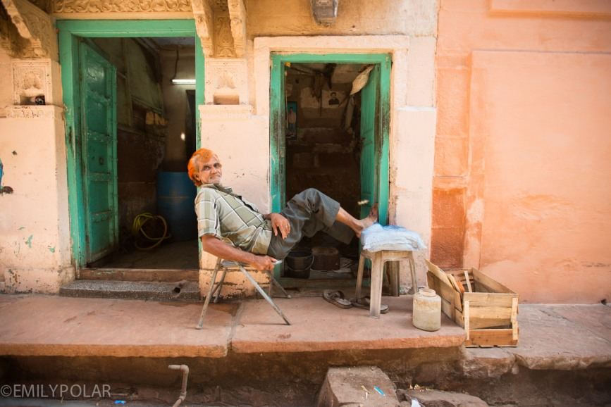 Indian man sitting on chair outside of his home in an alley of Jodhpur.
