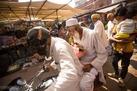 Two Indian men maneuver their way around the market on a motorcycle in Jodhpur.