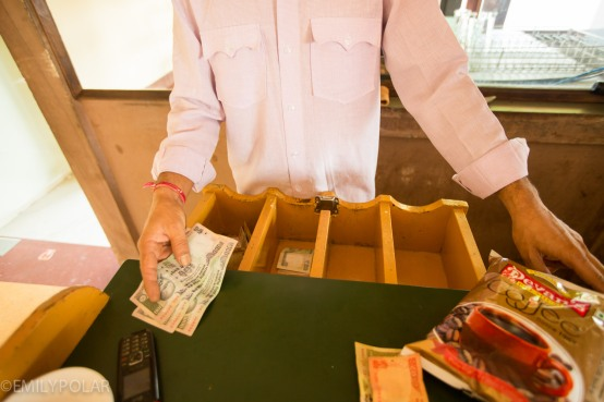 Indian man counting out change from cash drawer in cafe of Jodhpur.