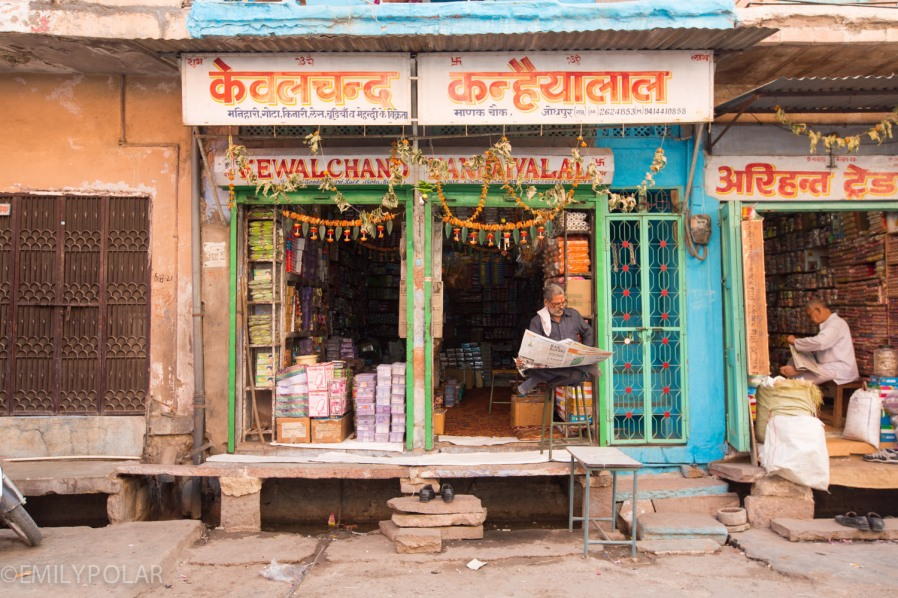 Indian man sitting outside his shop reading the paper in Jodhpur.