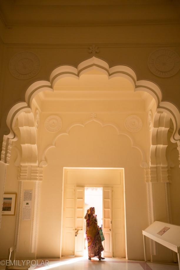 Woman walking into museum through arching doorways of Rajasthan, Jodhpur.