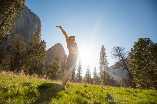 Man stretching in El Cap meadow at sunset on a spring day in Yosemite.