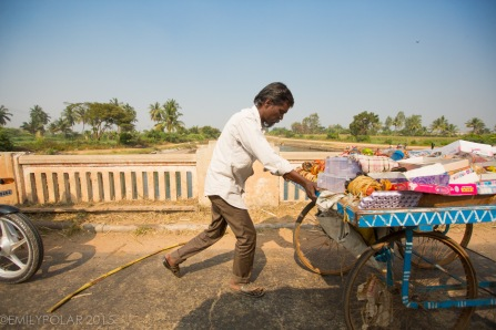 Indian man pushing cart with gifts and toys for sale down the road in Hampi, India.