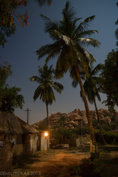Moon light shinning on a small home with the porch light on surrounded by palm trees at Goan Corner, Hampi.