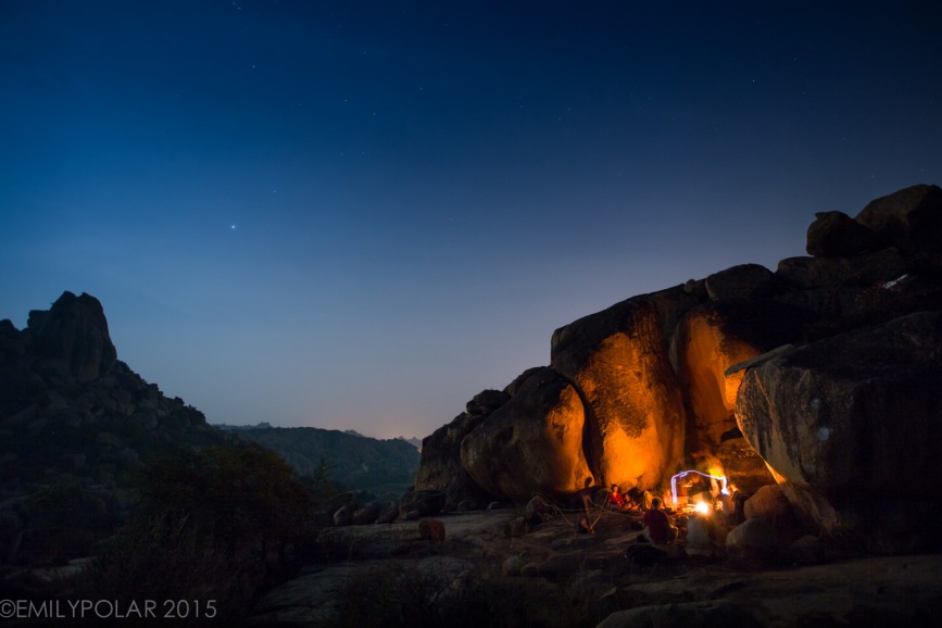 Climbing friends hanging out at campfire surrounded by glowing boulders under the stars in Hampi.
