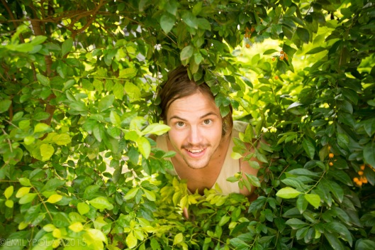 Climber pops his head out of a hole in the bushes at goan corner in Hampi.