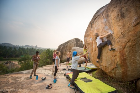 Woman climbing T.V. Boulder on the plateau in Hampi, India.