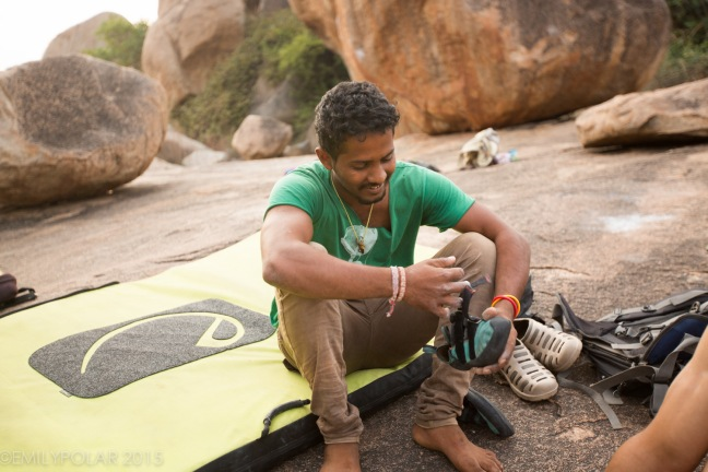 Climber sitting on crash pad putting on shoes in Hampi, India.