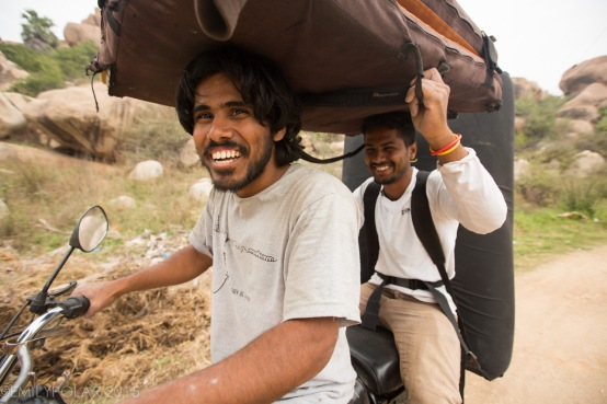 Climber friends riding on a scooter with crash pads down dirt road in Hampi, India.