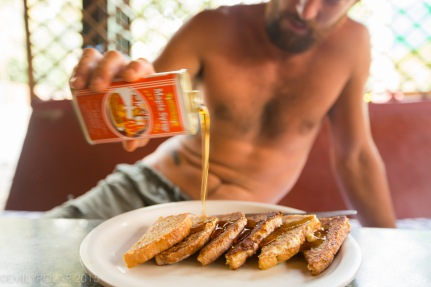 Man pouring maple syrup on french toast in Hampi.