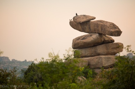 Stack of rocks with birds resting on the top at sunset near the lake in Hampi, India.