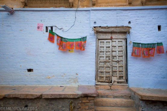 Blue wall with old wooden door chained and locked with lotus flags hanging on wall inside the Fort of Jaisalmer.