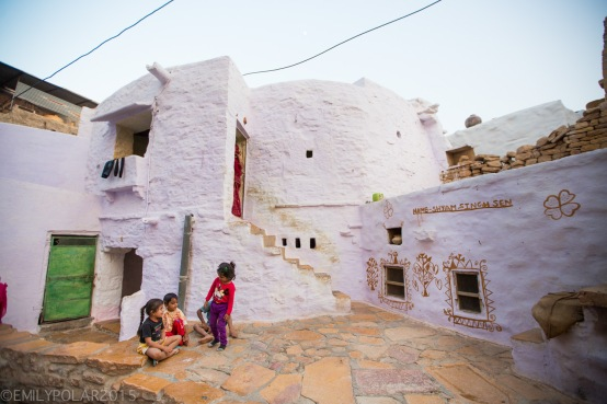 Indian boys and girls sit on the stone ground outside of their home in the Fort of Jaisalmer.