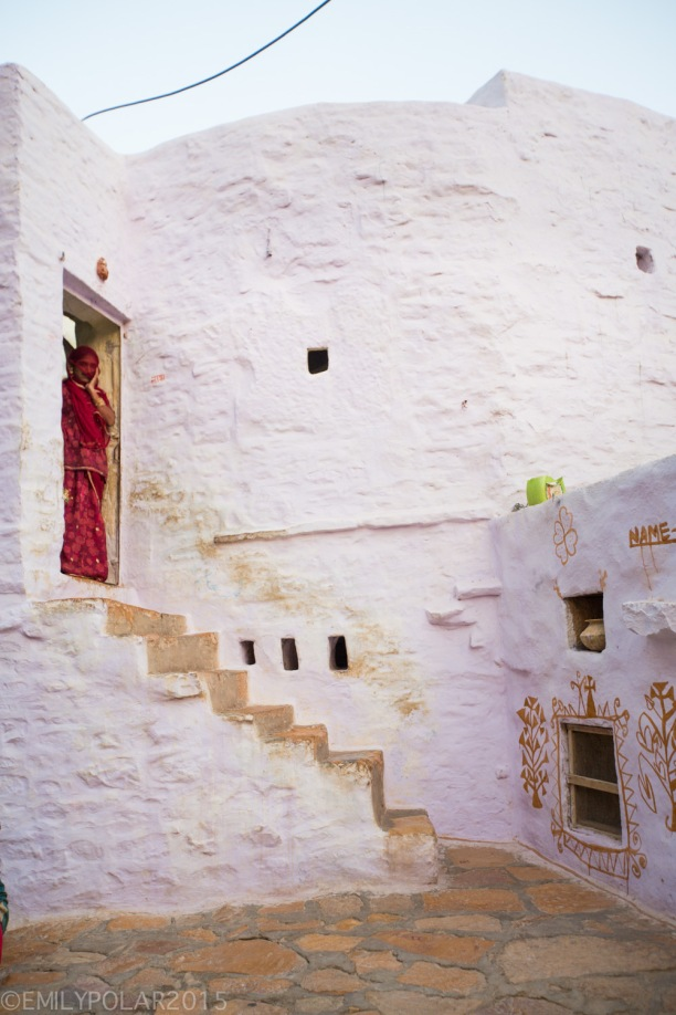 Indian woman in red sari covers her face standing in her doorway of a pink house inside Jaisalmer Fort.