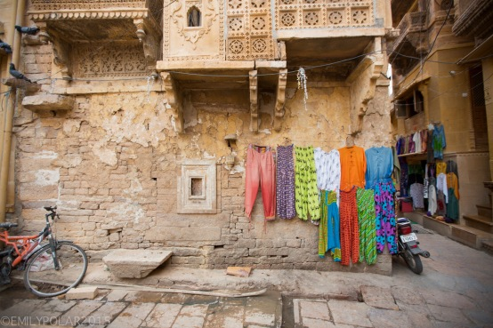 Colorful pants for sale hanging up on side of mud home inside the fort of Jaisalmer.