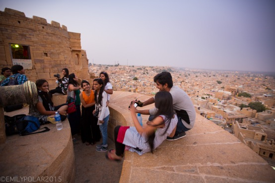 Group of teens hanging out on top of the fort at dusk in Jaisalmer.