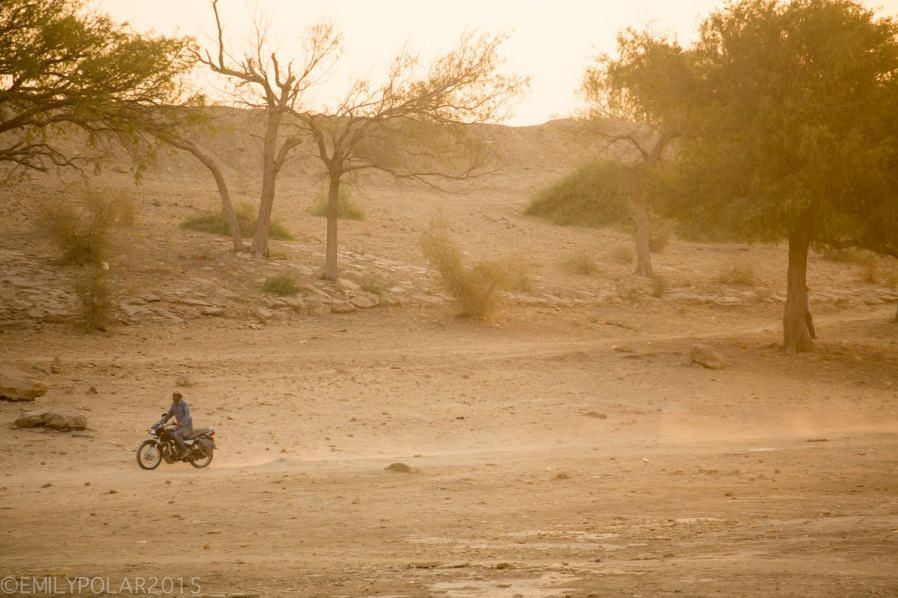 Golden morning sun shinning at Amar Sagar Temple complex while a man rides his motorcycle along a dirt path in Jaisalmer.