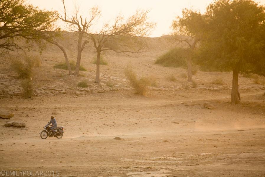 Golden morning sun shinning at Amar Sagar Temple complex while a man rides his motorcycle along a dirt path in Jaisalmer.