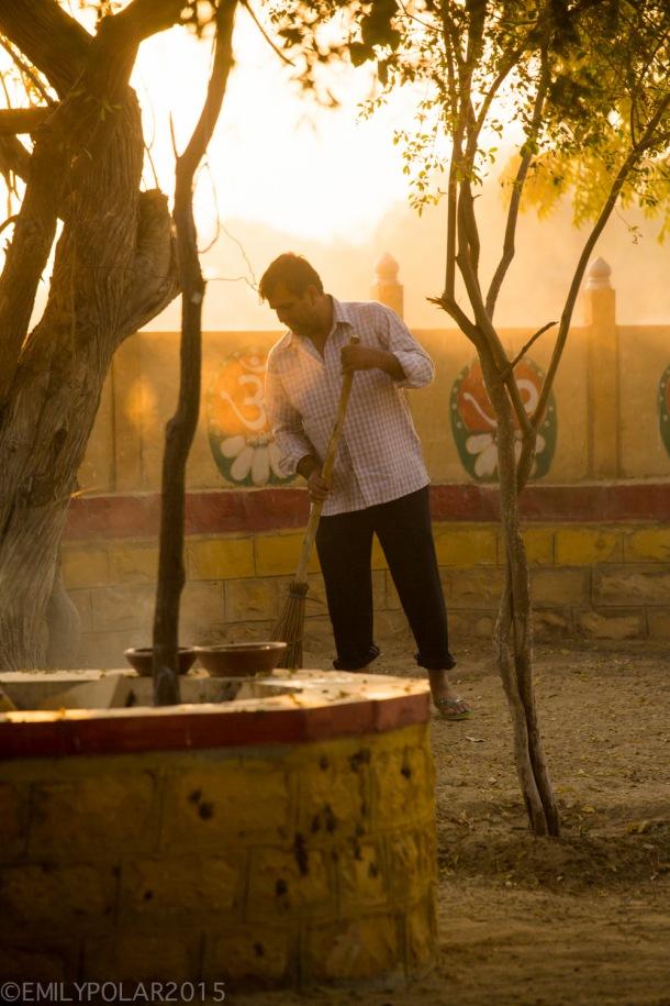 Indian man sweeping dust at sunrise at the temple at Sagar lake in Jaisalmer.