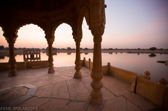 Warm glowing light at sunrise over lake Sagar at Amar Sagar temple in Jaisalmer.