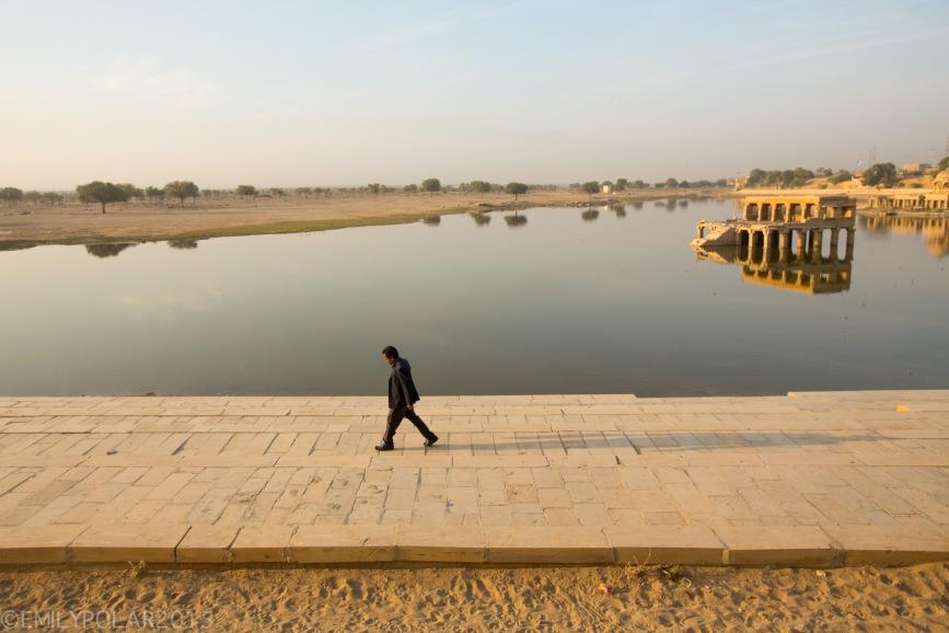 Indian man walking along Sagar lake at sunrise in Jaisalmer, India.