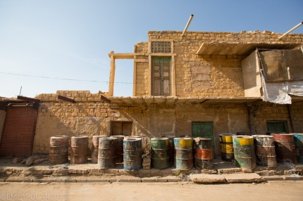 Barrels of paint stored outside mud brick home in the streets of Jaisalmer.