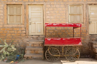 Red cart with cute wheels and cover sits outsid of home in the streets of Jaisalmer.