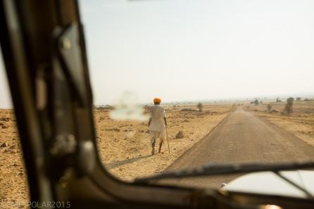 Rajasthani man with orange turban walking in the desert with a cane.