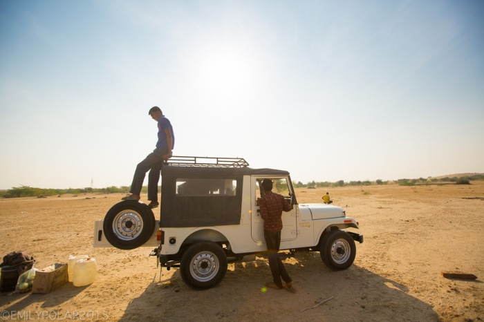 Local Rajasthani men take supplies of jeep in the desert for a camel safari with western tourists in the Thar desert.