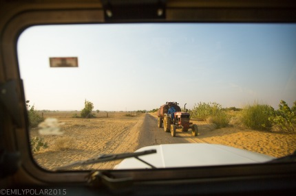View from the window of a jeep of a one lane road in the desert with a tractor in Rajasthan.