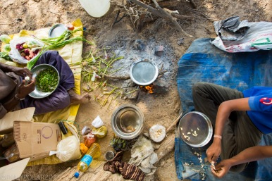 Rajasthani men prepare a vegetarian lunch over a campfire in the Thar desert, India.