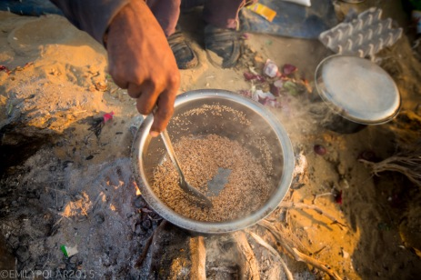 Indian man stiring pot of breakfast cereal in metal pot over camp fire in the desert of Jaisalmer.