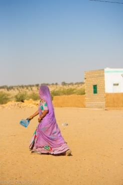 Indian woman wearing colorful safari sweeping in the dusty Thar desert.