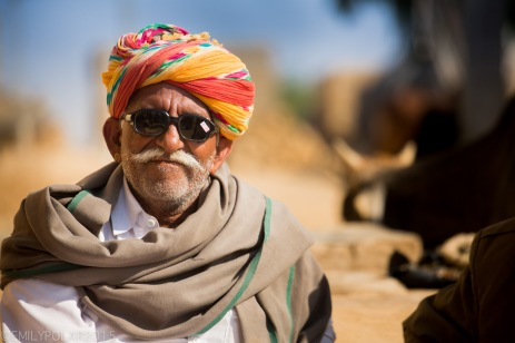 Rajasthani man wearing new sunglasses with sticker on them sitting in front of his mud home in a small village of Thar desert, India.